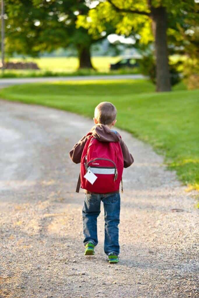 boy in brown hoodie carrying red backpack while walking on 207697